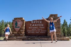 Two girls pose in silly positions at the Bryce Canyon National Park sign stock photo