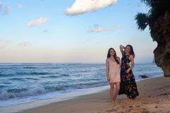 Two girls posing on the beach in front of the rock. At dawn Stock Photography