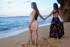 Two girls posing on the beach in front of the rock. At dawn Royalty Free Stock Image
