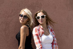 Two girls posing on a brown background wall, glasses, blonde and brunette Stock Photo