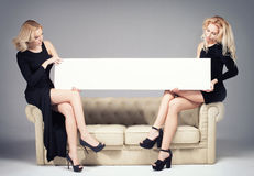 Two girls posing with empty board. Royalty Free Stock Photography
