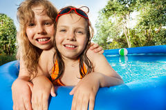 Two girls posing in the swimming pool at sunny day Royalty Free Stock Photo