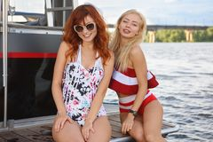 Two girls are posing on yacht royalty free stock image