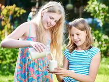Two girls pours milk in sunny meadow Royalty Free Stock Images