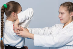 Two girls practice Aikido. Two girls in black hakama practice Aikido Stock Images