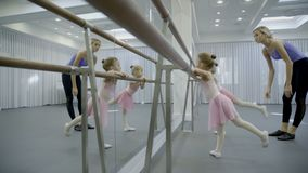 Two girls are practice near barre with coach in ballet studio. Little children lean with hands on bar, lifting one leg, caring teacher helps them to make right stock video footage