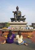 Two girls praying before the statue of king Ramkhamhaeng the Great in historical Park. Thailand Stock Image