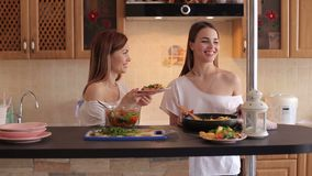 Two girls prepare Breakfast at home in the morning. Two young beautiful girls prepare a vegetable salad in the kitchen, have fun talking and laughing. Two stock footage