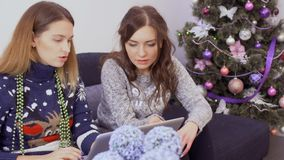Two girls prepares for holidays and choose Christmas gifts in the internet store. Two young girlfriends in sweaters sits on sofa at home and makes online stock video