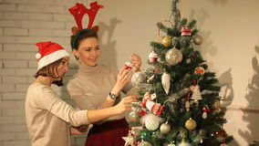 Two girls are preparing for Christmas and decorate the Christmas tree stock footage
