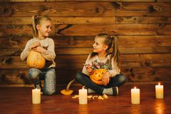 Two girls preparing for the holiday. Night, candles, pumpkin, tales. Girls make lamps out of pumpkins for Halloween stock photos