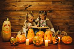 Two girls preparing for the holiday. Night, candles, pumpkin, tales. Girls read old skazki. Halloween. Lamps of pumpkins Stock Images