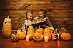 Two girls preparing for the holiday. Night, candles, pumpkin, tales. Girls read old skazki. Halloween. Lamps of pumpkins stock image