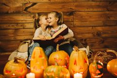 Two girls preparing for the holiday. Night, candles, pumpkin, tales. Girls read old skazki. Halloween. Lamps of pumpkins royalty free stock photography