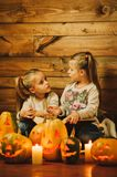 Two girls preparing for the holiday. Night, candles, pumpkin, tales. The girls are reading the old stories. Halloween. Lamps of pumpkins Royalty Free Stock Photos