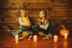 Two girls preparing for the holiday. Night, candles, pumpkin, tales. Girls make lamps out of pumpkins for Halloween Stock Photography