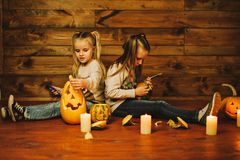 Two girls preparing for the holiday. Night, candles, pumpkin, tales. Girls make lamps out of pumpkins for Halloween Stock Image