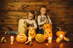 Two girls preparing for the holiday. Night, candles, pumpkin, tales. Girls make lamps out of pumpkins for Halloween Royalty Free Stock Image