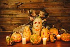 Two girls preparing for the holiday. Night, candles, pumpkin, tales. Girls make lamps out of pumpkins for Halloween Stock Photo