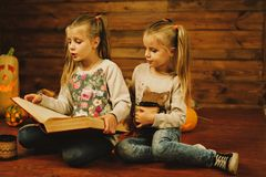 Two girls preparing for the holiday. Night, candles, pumpkin, tales. Two girls are reading an old book. Halloween stock photos