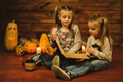 Two girls preparing for the holiday. Night, candles, pumpkin, tales. Two girls are reading an old book. Halloween Stock Image