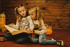 Two girls preparing for the holiday. Night, candles, pumpkin, tales. Two girls are reading an old book. Halloween royalty free stock photography