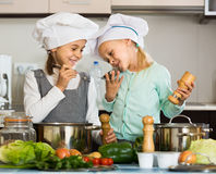 Two girls preparing vegetables and smiling indoors Stock Photo
