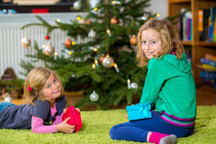 Two girls with presents in front of christmas tree Royalty Free Stock Photos