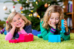 Two girls with presents in front of christmas tree Stock Photos