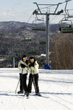 Two girls pretending they are cold on ski slope Stock Photography