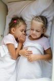 Two girls pretending that sleep on the bottom shelf in a train Royalty Free Stock Photo