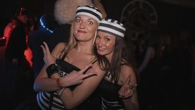 Two girls in prisoners costumes posing for camera at night club halloween party. Wide open eyes stock footage