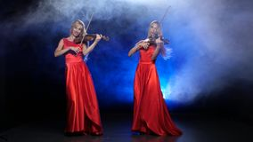 Two girls professional fiddlers playing the violin. Studio. Smoke. Two gorgeous blonde, professional fiddlers, with long hair, playing the violin professional stock video footage