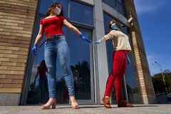 Two girls in protective masks and medical gloves keep distance in quarantine outdoors, in coronavirus disease COVID-19.