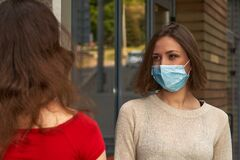 Two girls in protective masks are talking and keep distance in quarantine outdoors, in coronavirus disease, COVID-19 epidemic