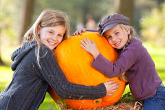 Two girls proud of their big pumpkin Stock Photo