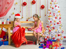 Two girls pulled out a bag of Christmas gifts Santa Claus. Two funny sisters four girls and six years of playing and having fun in the home New Years interior Royalty Free Stock Photography