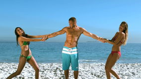 Two girls pulling arms of a handsome friend. Then falling on the beach in slow motion stock video