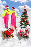 Two girls pulling Santos on a sled Stock Photography