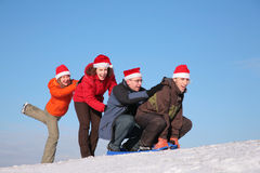 Two girls push two men on sled Stock Image
