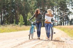 Two girls pushing bicycles and walking Royalty Free Stock Photography