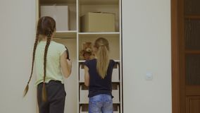 Two girls put their things into a cupboard after the relocation in a new house. Cute sisters turns to camera, looks in it and smiling. Happy girls in a new stock video footage