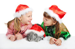 Two girls with a rabbit in caps of Santy. On white stock image