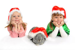 Two girls with a rabbit in red caps of Santy. Over white stock photo