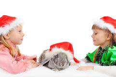 Two girls with a rabbit in red caps of Santy Stock Photo