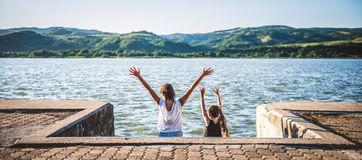 Two girls with raised hands standing on river dock Stock Images