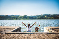 Two girls with raised hands standing on river dock Royalty Free Stock Photo
