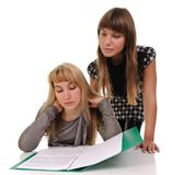 Two girls read documents. Stock Images