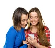 Two girls read messages by phone Stock Image