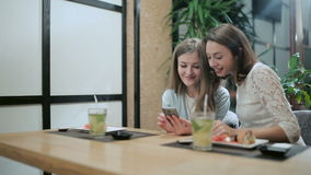 Two girls read something on the phone and laughing. Two girls are considering something on smartphone while sitting with sushi rolls and mojito in asian stock footage